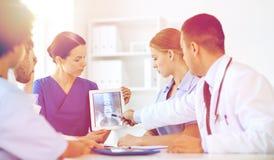 Grupp av doktorer med röntgenstrålen på minnestavlaPC på kliniken Arkivfoto