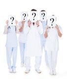 Grupp av doktorer med tecknet för frågefläck arkivfoto