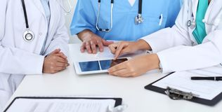 Grupp av doktorer på det medicinska mötet Stäng sig upp av läkaren som använder handlagblocket eller minnestavladatoren fotografering för bildbyråer