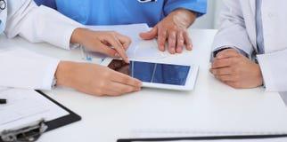 Grupp av doktorer på det medicinska mötet Stäng sig upp av läkaren som använder handlagblocket eller minnestavladatoren royaltyfri bild