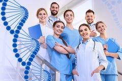Grupp av doktorer på kliniken och DNAformeln arkivbild