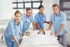 Grupp av doktorer som bär kvinnapatienten Arkivfoto