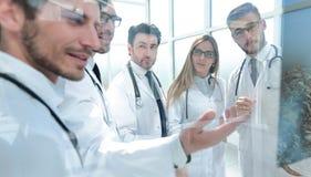 Grupp av doktorer som diskuterar patientens röntgenstråle royaltyfria foton