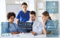 Grupp av doktorer som diskuterar röntgenstrålebildläsning på sjukhuset Royaltyfria Foton
