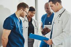 Grupp av doktorer som läser ett dokument arkivfoton
