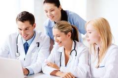 Grupp av doktorer som ser minnestavlaPC royaltyfri bild