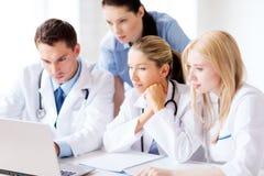 Grupp av doktorer som ser minnestavlaPC fotografering för bildbyråer