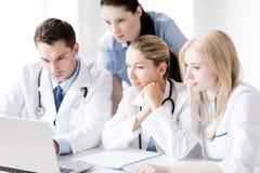 Grupp av doktorer som ser minnestavlaPC Royaltyfri Fotografi