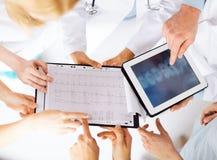 Grupp av doktorer som ser röntgenstrålen på minnestavlaPC Royaltyfri Foto