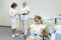 Grupp av doktorer som ser röntgenstrålen Tand- kontor, barnpatient i fåtölj Sjukvård-, läkarundersökning- och tandläkekonstbegrep arkivfoto
