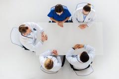 Grupp av doktorer som sitter på den tomma tabellen Arkivfoton