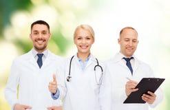 Grupp av doktorer som visar tummar upp över vit royaltyfria bilder