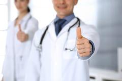 Grupp av doktorer som visar upp tummar Perfekt medicinsk service i klinik Lycklig framtid i medicin- och sjukvårdbegrepp royaltyfri foto