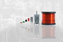 Grupp av elektronikdelen med kopparspoleferrite, kondensator, r arkivfoton