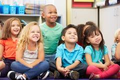 Grupp av elementära elever i klassrum Arkivbild