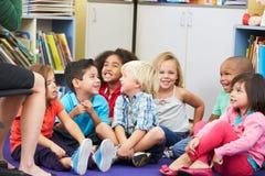 Grupp av elementära elever i klassrum som lyssnar till läraren Arkivfoto