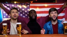 Grupp av emotionella amerikanska fans som stöttar den favorit- laginnehavflaggan, strid arkivfoton
