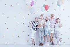 Grupp av entusiastiskt äldre folk med färgrika ballonger royaltyfria bilder