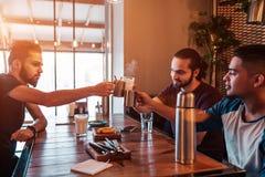 Grupp av exponeringsglas för finka för unga män för blandat lopp i vardagsrumstång Blandras- vänner som har gyckel i kafé arkivfoton