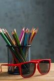 Grupp av färgblyertspennor och röd solglasögon i en ställning Arkivfoton