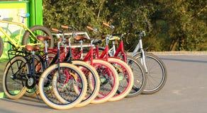 Grupp av färgrika cyklar som tillsammans parkeras i en parkeringsplatscloseup royaltyfri foto