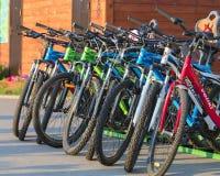 Grupp av färgrika cyklar som tillsammans parkeras i en parkeringsplatscloseup royaltyfria foton