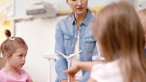 Grupp av förskole- barn och modell av vindturbinen stock video