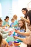 Grupp av förskole- ungar som drar med blyertspennor och limmar med limpinnen på konstgrupp i dagis- eller daycaremitt arkivfoton