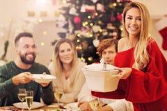 Grupp av familj och vänner som firar julmatställen Arkivbild