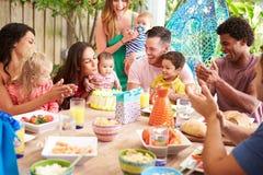 Grupp av familjer som hemma firar barns födelsedag royaltyfria bilder