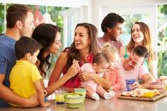 Grupp av familjer som hemma tycker om mellanmål fotografering för bildbyråer