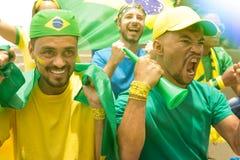 Grupp av fans som håller ögonen på en match och hurrar det brasilianska laget fotografering för bildbyråer