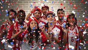 Grupp av fans som hurrar för deras lag med konfettier stock video