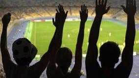 Grupp av fans som hurrar för fotbollslagseger på fullsatt stadion, konkurrens lager videofilmer