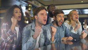 Grupp av fans som tycker om sportleken som extremt är lycklig om segern som kopplar av i stång stock video