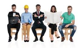 Grupp av fem olika personer som väntar på en jobbintervju royaltyfri fotografi