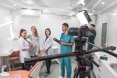 Grupp av filmskapare som skjuter en film i en tandläkekonst arkivbilder