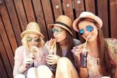 Grupp av flickavänner som dricker sodavatten på pir arkivbilder