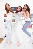 Grupp av flickavänner som hemma hoppar ha partiet Royaltyfri Bild