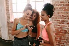 Grupp av flickor i konditiongrupp som ser smartphonen Royaltyfri Foto