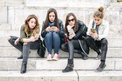 Grupp av flickor med smartphones Teknologiisolering och emotio Royaltyfria Bilder