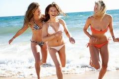 Grupp av flickor på strandferie Arkivbild