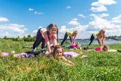 Grupp av flickor som gör som sträcker öva utbildning utomhus arkivbilder