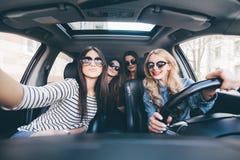Grupp av flickor som har gyckel i bilen och tar selfies med kameran på vägtur fotografering för bildbyråer