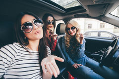 Grupp av flickor som har gyckel i bilen och tar selfies med kameran på vägtur arkivfoto