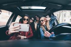 Grupp av flickor som har gyckel i bilen och tar selfies med kameran på vägtur Royaltyfria Bilder