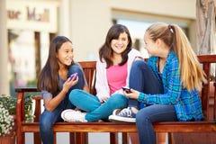 Grupp av flickor som sitter i galleria genom att använda mobiltelefoner arkivfoton