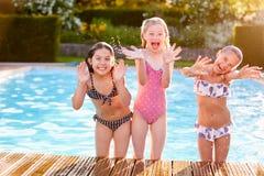 Grupp av flickor som spelar i utomhus- simbassäng Fotografering för Bildbyråer