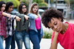 Grupp av flickor som trakasserar en afrikansk amerikankvinna royaltyfri bild