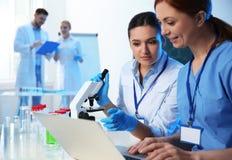 Grupp av forskare som arbetar i kemilaboratorium royaltyfria bilder